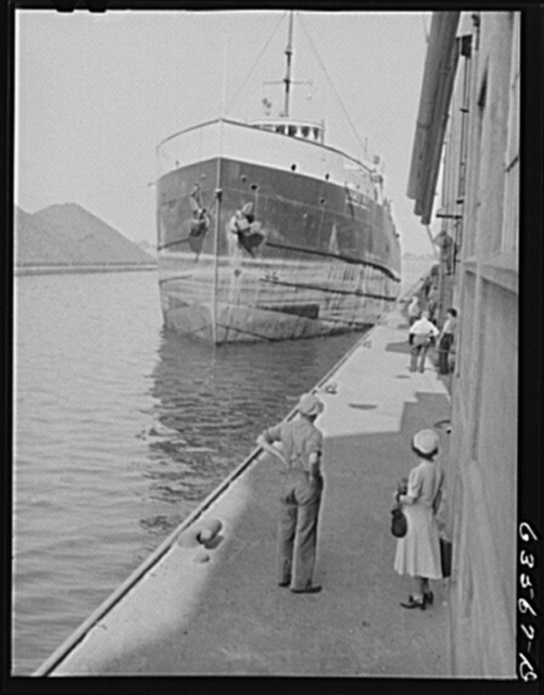 Boat coming in light to take load of grain to Buffalo. Grain elevator superintendant and sailor's wife waiting in foreground. Duluth, Minnesota