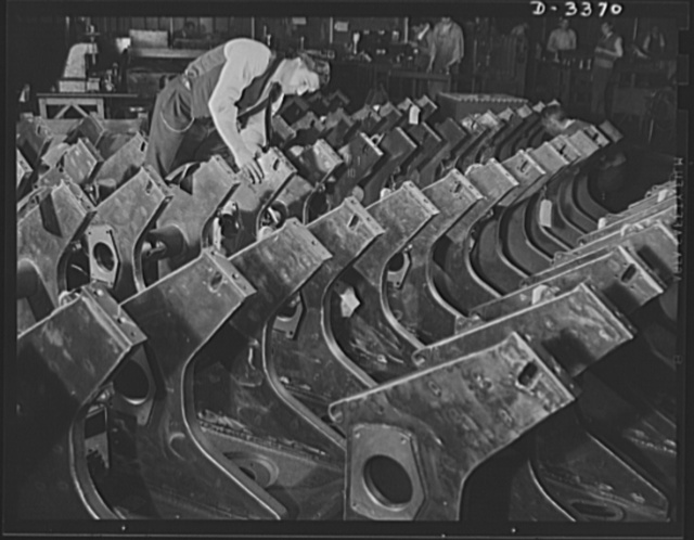 Bofors forty-millimeter mounts. A plant inspector carefully checks welded gun carriages for Bofors forty-millimeter anti-aircraft guns. These carriages and Bofor gun mounts are now manufactured in a large Midwest rubber company which has been converted to production of war necessities. Originally, Bofors carriages were riveted and required many additional operations in assembling, but company engineers have produced this welded construction which has reduced time and cost of manufacture and produced a much stronger, one-piece article