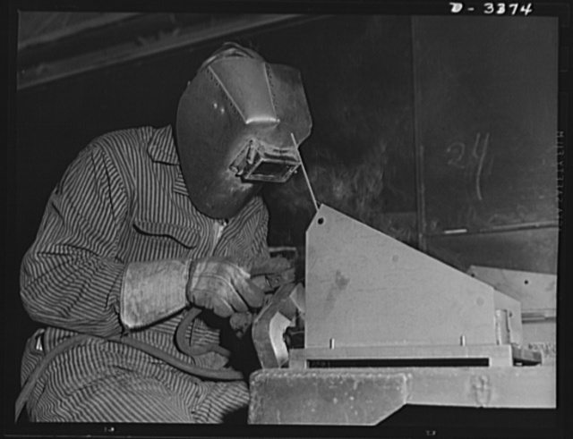 Bofors forty-millimeter mounts. He has a vital job in the manufacture of forty-millimeter Bofors gun mounts and carriages. This arc welder wearing a protective mask is completing a skilled operation on part of a gun mount in a large Midwest rubber factory now converted to war production