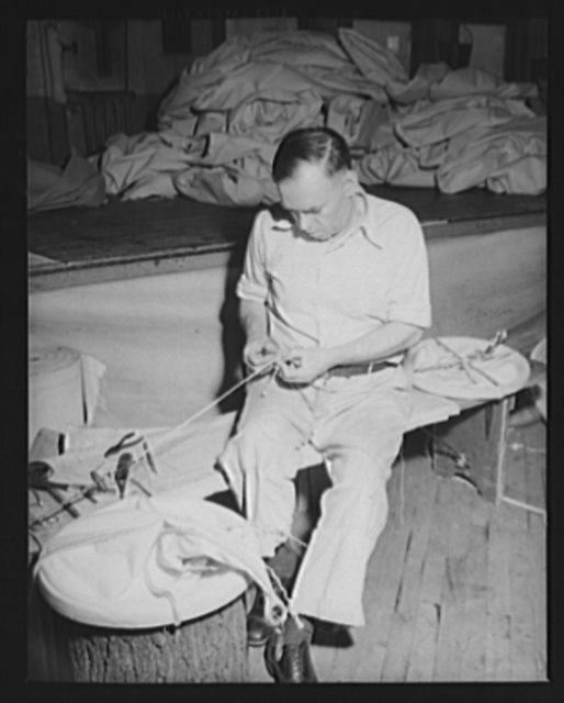 Boy scout training helps. He may not have learned to tie knots from a Scoutmaster, but this worker at an eastern Navy yard has plent on hand. He's manufacturing canvas accessories in the yard's sail-loft