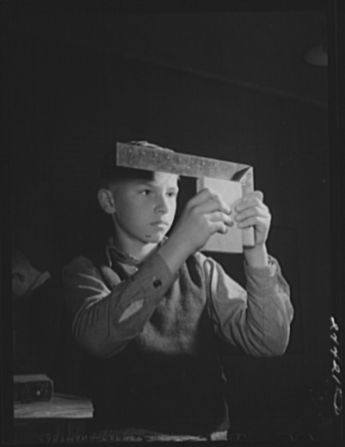 Boy using right angle square in woodworking shop at the homestead school. Dailey, West Virginia