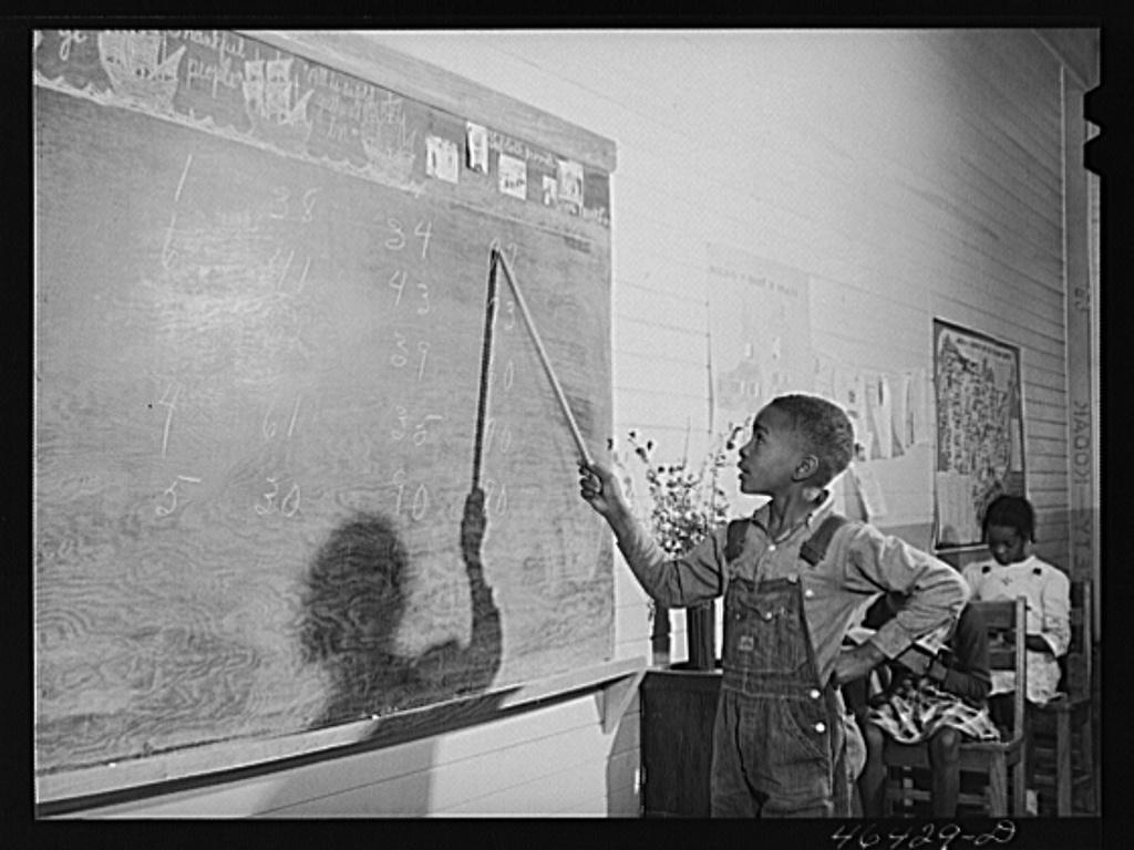 Boyd Jones doing his arithmetic lesson at the blackboard in the Alexander Community School in Greene County, Georgia