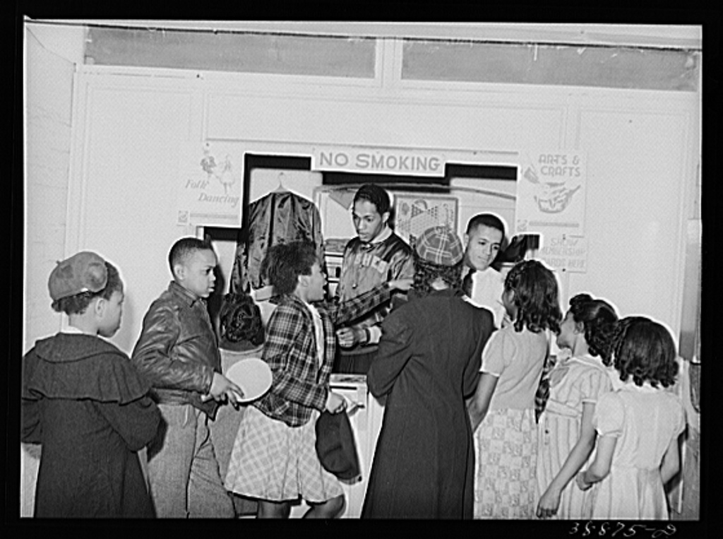 Boys and girls presenting membership cards at recreational booth in basement of the Good Shepherd Community Center. Chicago, Illinois