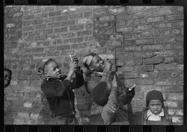 Boys playing that they are shooting machine guns at a passing aeroplane, Black Belt, Chicago, Illinois