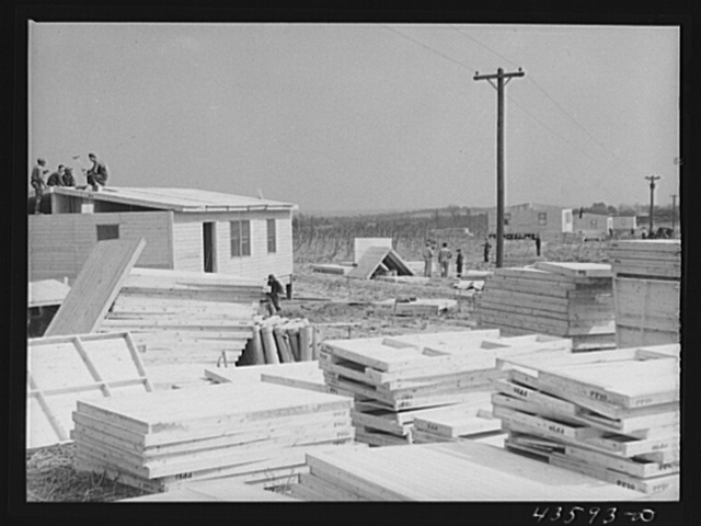 "Building prefabricated houses for farmers who had to move out of the Camp Croft area. ""Ready made"" sections are in foreground. Pacolet, South Carolina region"