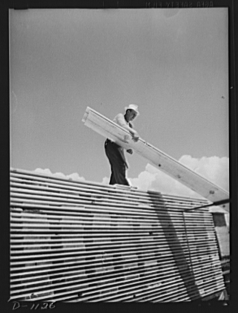 Building stockpiles. Ponderosa pine boards being stacked in a western sawmill. Efforts are being made (June 1941) to create a stockpile of lumber to insure a steady monthly output of ammunition cases. Lumber is also supplied from these mills for the construction of barracks and cantonments