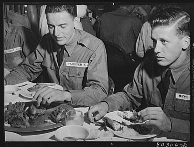"Cadet E.A. Peresich Jr. takes his third helping of fried chicken. Craig Field, Southeastern Air Training Center, Selma, Alabama (FSA (Farm Security Administration) ""Food for Defense"")"