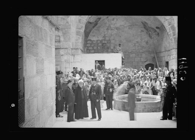 Calendar of religious ceremonies in Jer. [i.e., Jerusalem] Easter period, 1941. Neby Mousa [i.e., Nebi Musa] banners presented by Mr. Keith Roach. Group inside the old bld'g, large gathering