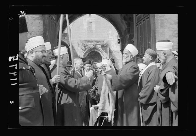Calendar of religious ceremonies in Jer. [i.e., Jerusalem] Easter period, 1941. Neby Mousa [i.e., Nebi Musa] banners presented by Mr. Keith Roach. Sheik Aaref handing banner to bearer