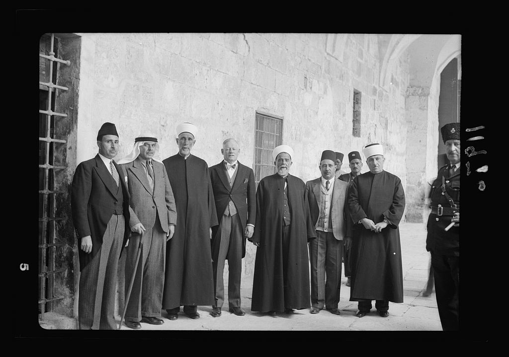 Calendar of religious ceremonies in Jer. [i.e., Jerusalem] Easter period, 1941. Neby Mousa [i.e., Nebi Musa] banners presented by Mr. Keith Roach. Group outside old religious court in mosque grounds with K.R. [i.e., Keith Roach]. etc. & sheiks