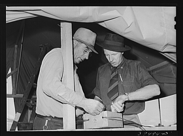 Camp manager, right, and engineer, left, check electrical connection. Mobil unit, FSA (Farm Security Administration) labor camp. Nampa, Idaho