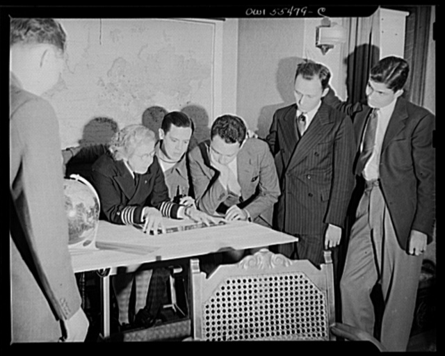 """""""Captain"""" Mary Converse, instructing V-7 (candidates for United States Navy ensign commissions) students in use of sextant, compass and gyroscope and in navigation. A problem in charting a course takes shape; every member of the class is keenly interested"""