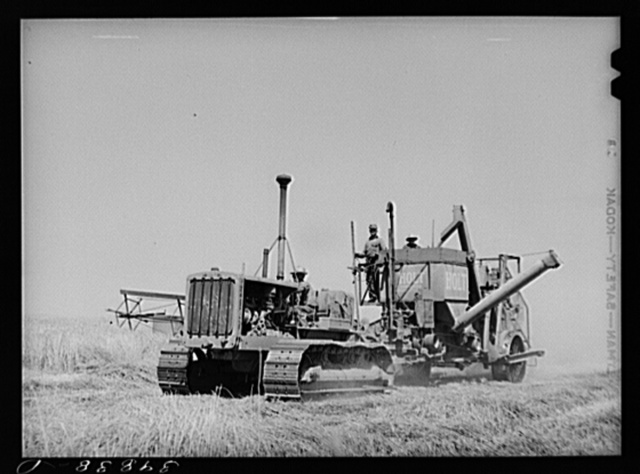 Caterpillar tractor and combine in wheat field on Eureka Flats. Walla Walla County, Washington