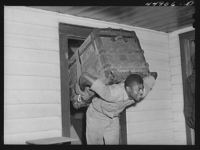 CCC (Civilian Conservation Corps) boy carrying a trunk out for a family who is moving out of the area taken over by the Army for maneuver grounds. Caroline County, Virginia