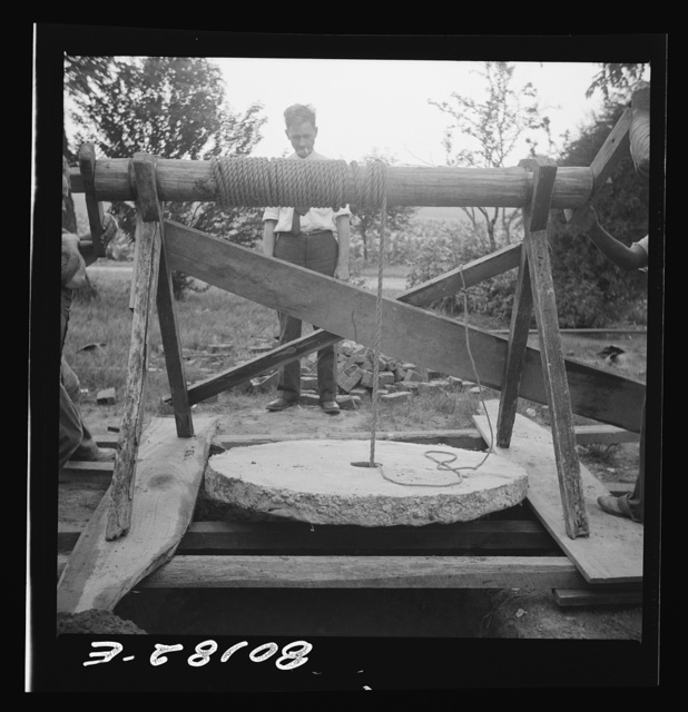 Cement cap hanging in windlass prior to lowering into well. John Hardesty well project, Charles County, Maryland