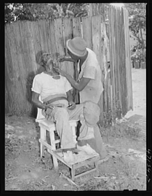 Charlotte Amalie, Saint Thomas Island, Virgin Islands. An outdoor barber shop in a slum area near the waterfront
