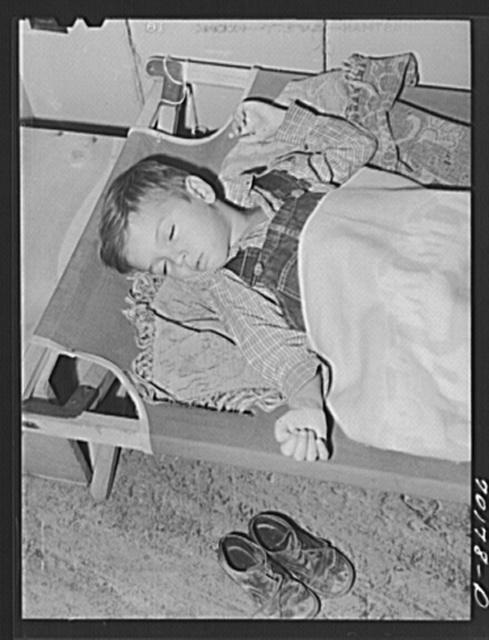Child of farm worker takes a nap at the nursery school at the FSA (Farm Security Administration) farm family migratory labor camp. Yakima, Washington
