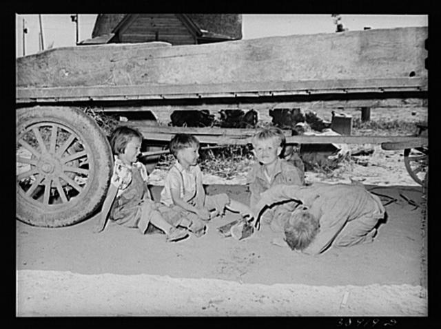 Children playing under wagon at the Schroder farm, FSA (Farm Security Administration) rehabilitation borrowers living on Dead Ox Flat. Vale-Owyhee irrigation project, Malheur County, Oregon