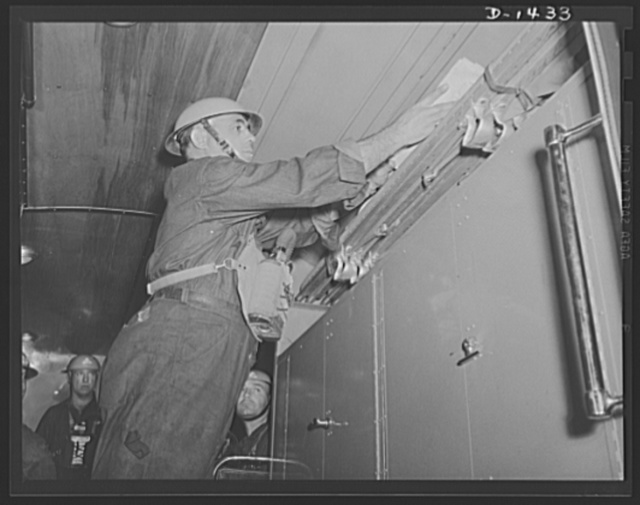 Civilian defense. Removing blankets and stretchers from the special compartment in the New York Emergency Service truck. The lower compartment contains a portable searchlight of 1000 candle power