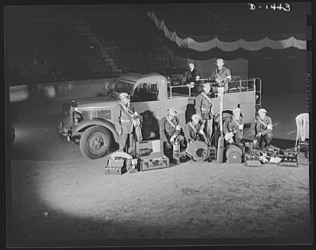 Civilian defense. There's not much that is omitted in the equipment of these special gas and electrical emergency trucks. On the floor in front of the trunk are, left to right, the following items: a fitter's kit for repairing small gas leaks; a rubberized blanket for electrical work; an atmosphere testing machine; an inhalator; a Phister fire extinguisher; an air blower ; a lux fire extinguisher kit; a splicer's kit containing insulated hand tools; a fuse kit; a manhole guard rail and a rubber mat for electrical work. The worker at the left is wearing a special mask with a half-hour suplly of oxygen for use where a fresh air hose is not practical. He is also wearing rubber gloves for repair work. The man standing in the center is holding a hand operated manhole pump. The truck and its equipment were on display at Madison Square Garden, New York, as part of the huge civilian defense show held there in October