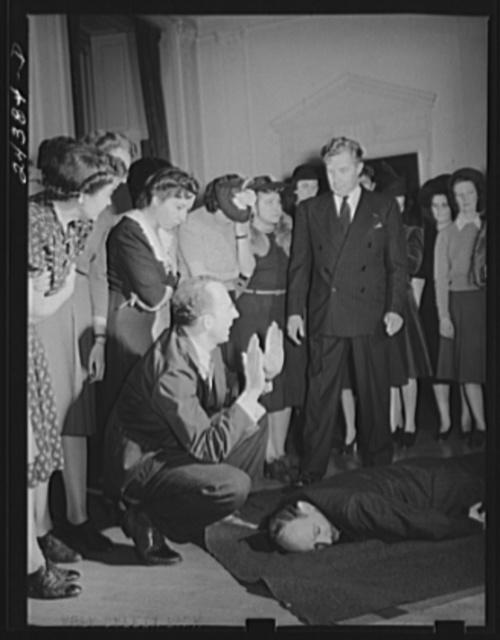 Civilian defense volunteers receiving instruction in proper care for man with spine injury. First aid class. American Red Cross, New York City