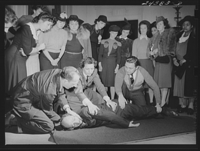 Civilian defense volunteers receiving instruction in proper care for man with spine injury. The first aid class of the American Red Cross, at New York City