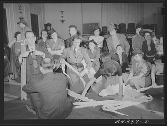 Civilian Defense volunteers receiving instruction in treatment of fractured arm. First aid class. American Red Cross, New York City