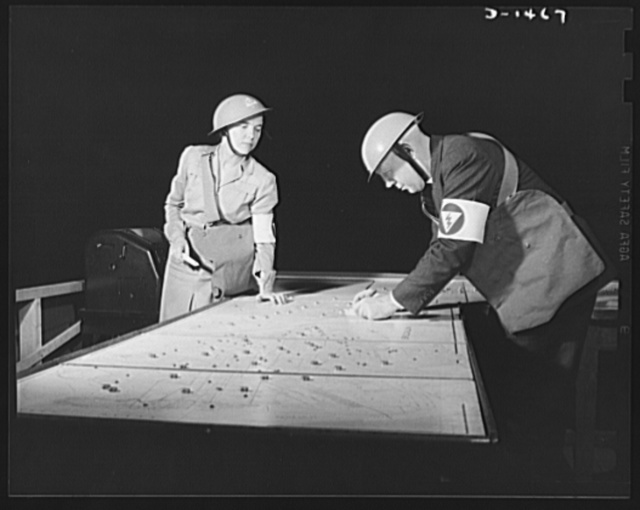 Civilian defense. Who goes where and when is decided by the controller of the plotting board, who assigns radio equipped units to the trouble areas. Here he is receiving information from a telephone operator. This is a vital part of civilian defense work. The demonstration was at the October 1941 civilian defense show in Madison Square Garden, New York