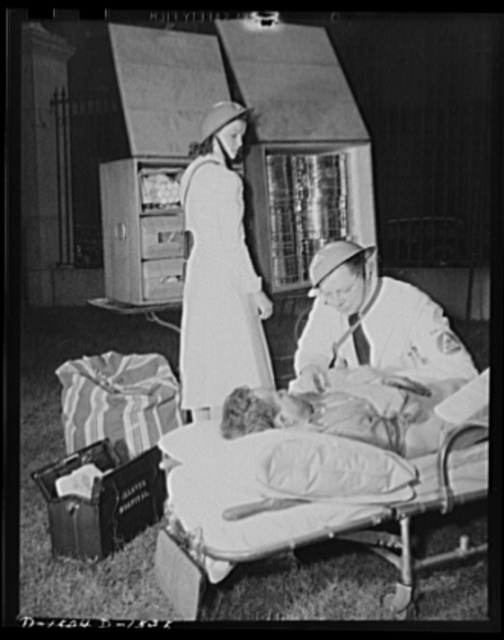 "Civilian protection. An emergency unit gives first aid in the field and examines the victim of a fallen bomb. After treatment, he will be quickly evacuated to the nearest hospital or bandaged and turned over to an emergency housing unit. The ""M.D."" next to the caduceus on the doctor's armband indicated that he is a registered physician"