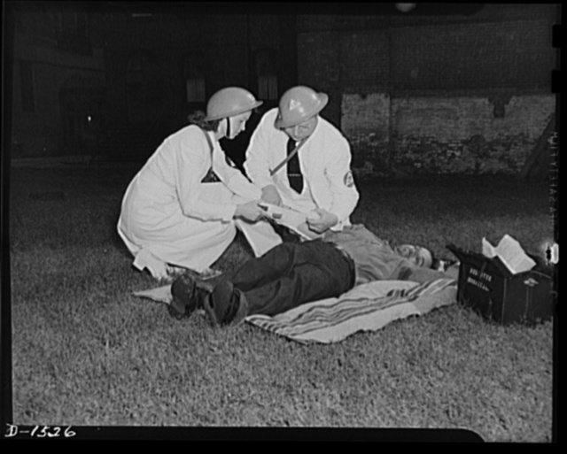 "Civilian protection. First Air treatment is the field to the victim of an emergency by members of a first aid group, in this case consisting of a doctor, denoted by the ""M.D."" and caduceus on the armband, and a nurse's aide"
