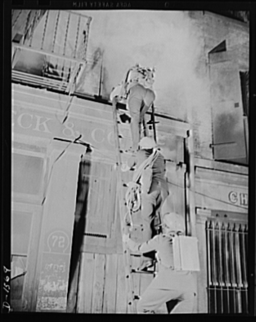 """Civilian protection. Fully equipped to cope with any situation they may encounter these New York City volunteer auxiliary firemen put on a demonstration of the matter in which they would handle the damage caused by an incendiary bombing attack. An incendiary bomb has fallen through the roof of this building and is blazing in the second story. One worker has already entered through the window and is using an """"Indian"""" fire pump on the small blaze which has started. His fellow workers are following up the ladder equipped (from top to bottom) with the following items: top man carries a portable acetylene torch used to cut through metal to effect entrance or to extricate occupants caught under fallen beams or pipes; the next man carries a roof rope, while the man at the bottom bears a two-way portable radio. All workers are supplied with gas masks"""