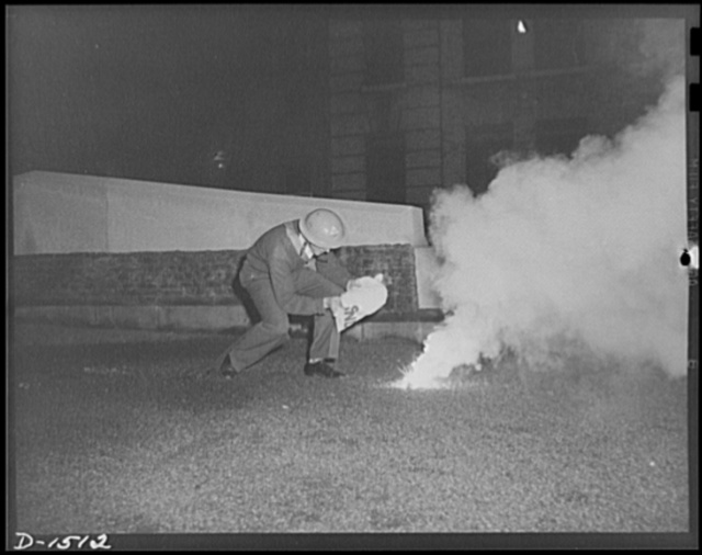 Civilian protection. This volunteer civilian defense worker, an auxiliary fireman, is preparing to extinguish an incendiary bomb. He carries the sandbag before his face to protect him from the molten magnesium sizzling forth like fat from a frying pan. He will drop the whole bag on the bomb, and the heat of the bomb will burn through the burlap, releasing the sand. The sand will then run onto and around the bomb.