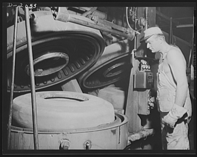 "Closing the cover of the mold. Entirely automatic, the ""watch-case"" mold is closed by pushing a button, which starts several operations. First the airbag is filled with live steam which circulates during the entire process; next an automatic timer sets itself for the proper length of time and temperature; next pressure is exerted to squeeze the tire into the mold pattern. Firestone (General) Tires, Akron, Ohio"