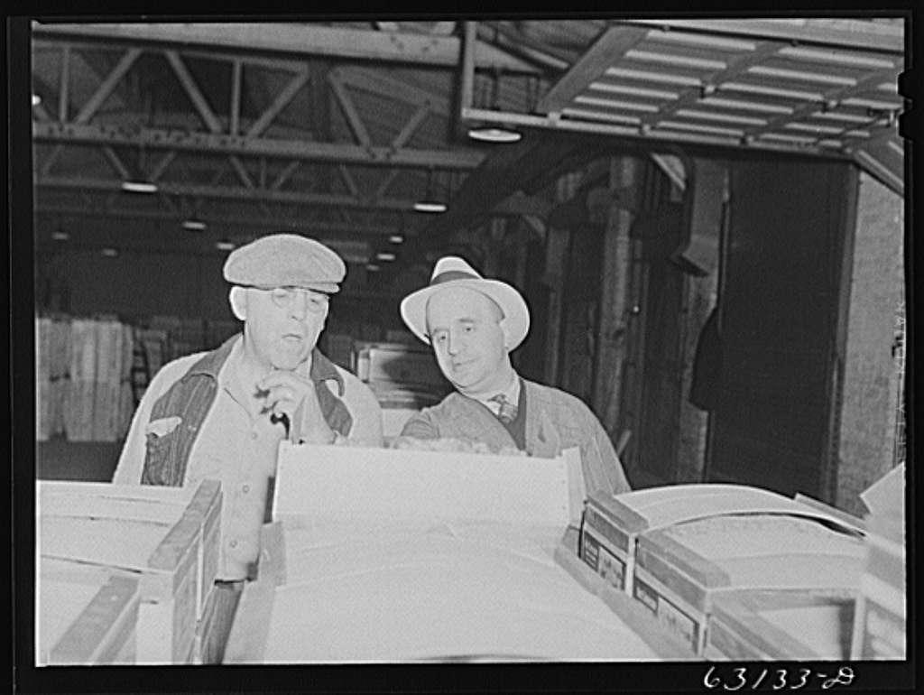Commission merchant examining produce at fruit warehouse. Chicago, Illinois