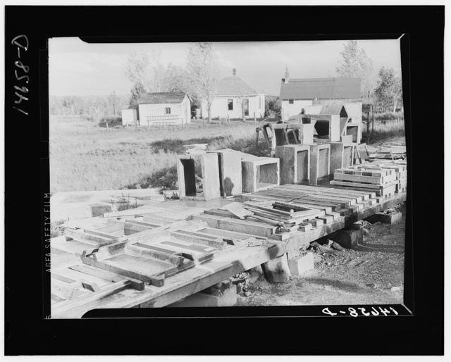 Concrete floor slabs, mud sills, and riser stools poured at central shop yard for farmers in Minnesota. Central construction permits economy in use of material. Minnesota