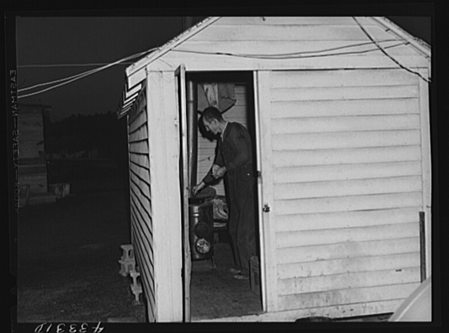 Cooking the evening meal in one of the bunkhouses at a settlement of workers from Fort Bragg. Near Manchester, North Carolina