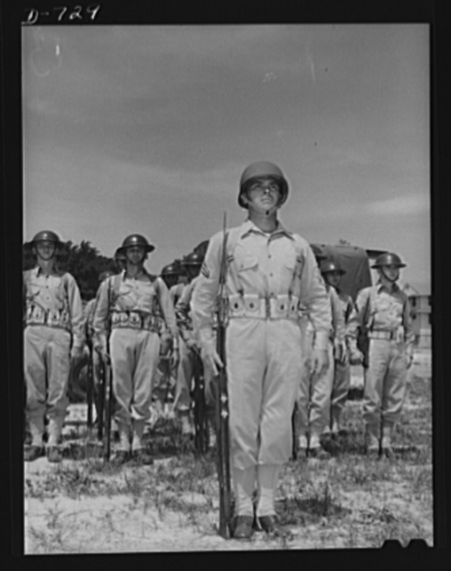 "Corporal French L. Vineyard and squad standing at attention. All the men are members of Company M, 12th Infantry. Corporal Vineyard is wearing the new ""pot type"" of helmet. The other members of the squad are wearing the old or ""basin type"" of helmet. Arlington Cantonment, Arlington, Virginia"