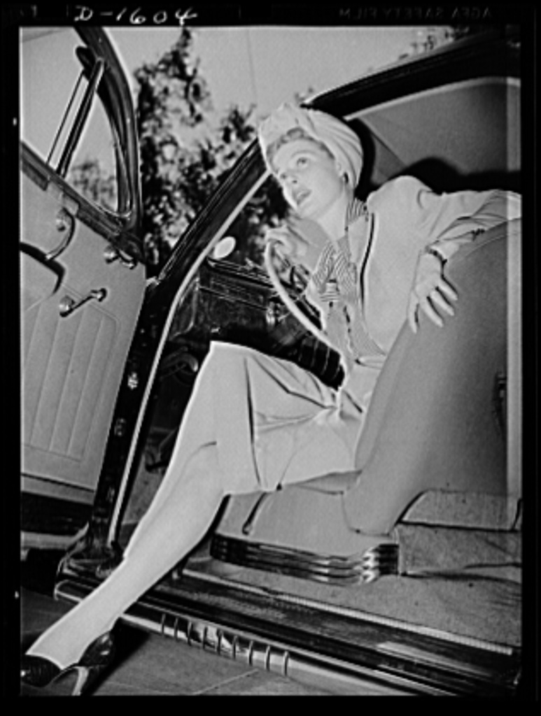 """Cotton stockings. Ann Sheridan wears a gabardine suit, skin tone hose with a clock design worked in at the ankle. This photograph demonstrates to some extent, the elasticity and sheerness of the new types of cotton stockings. The cotton hose now being made have more """"give"""" and """"twist"""" than the old type of cotton yarn"""
