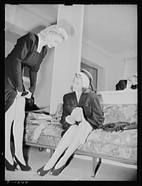 Cotton stockings. Cotton is coming to have a universal appeal. Shopping for cotton hose in a Hollywood store, Rita Hayworth finds that the shop-girl, too, is wearing hose much the same type she plans to buy. Miss Hayworth is inspecting a diamond pattern lisle stocking, personally selected for her by Hollywood's famed designer, Howard Greer, to accompany her afternoon emsemble