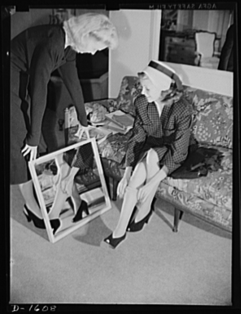 Cotton stockings. Cotton is coming to have universal appeal. Shopping for cotton hose in a Hollywood store, Rita Hayworth finds that the shop girl, too, is wearing hose much the same type she plans to buy. Miss Hayworth is inspecting a diamond pattern lisle stocking personally selected for her by Hollywood's famed designer, Howard Greer, to accompany her afternoon emsemble