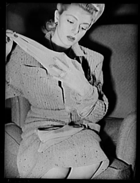 Cotton stockings. Lana Turner inspecting the ankle-flattering bracelet design embroidered on dressy, fine point lisle cotton mesh hose