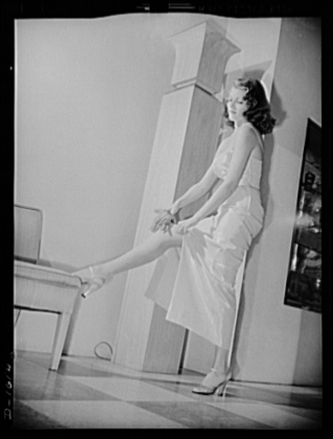 Cotton stockings. Rita Hayworth in a pink and silver lame evening dress, designed by the famed Hollywood designer, Howard Greer. Her evening hose are of fine crepe lisle of the same spun sugar sheen as the dress