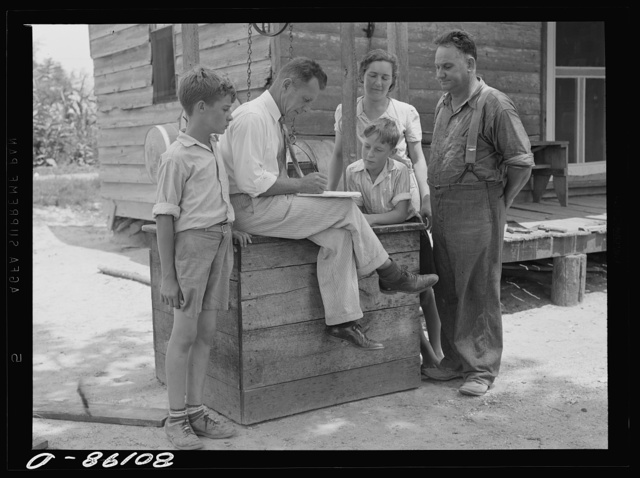 County supervisor talking over home plan with the Hardesty family resting on removed well top. Charles County, Maryland