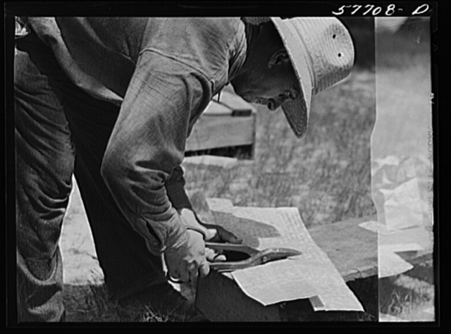Cutting metal reinforcing for corners. Screen door construction demonstration. Charles County, La Plata, Maryland