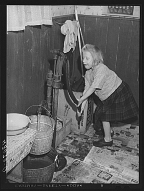 Daughter of a worker at the Pittsburgh Crucible Steel Corporation of Midland, Pennsylvania. Her father is at present in bed as a result of a leg injury at the mill. There are seven children and they help out by selling magazines from door to door. The pump is the only source of water