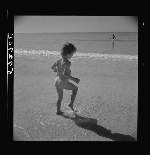 Daughter of parents living at Sarasota trailer park, Sarasota, Florida, playing in the water at the beach