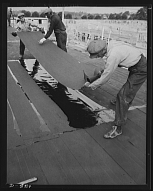 Defense housing, Erie, Pennsylvania. A built-up flat roofing is applied to the individual unit. Here workmen are laying the last covering before the finished coat