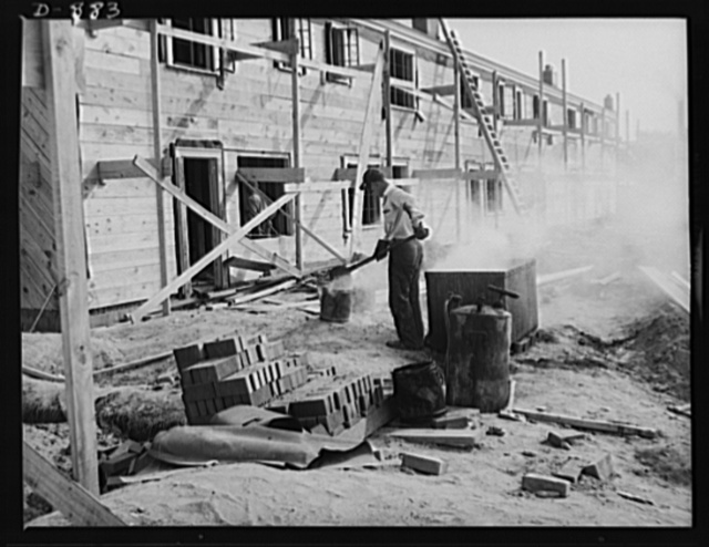 Defense housing, Erie, Pennsylvania. A built-up roofing is applied to the individual unit. Here a workman tends to the vat in which the pitch is kept molten. Pitch is hoisted to the roof in buckets