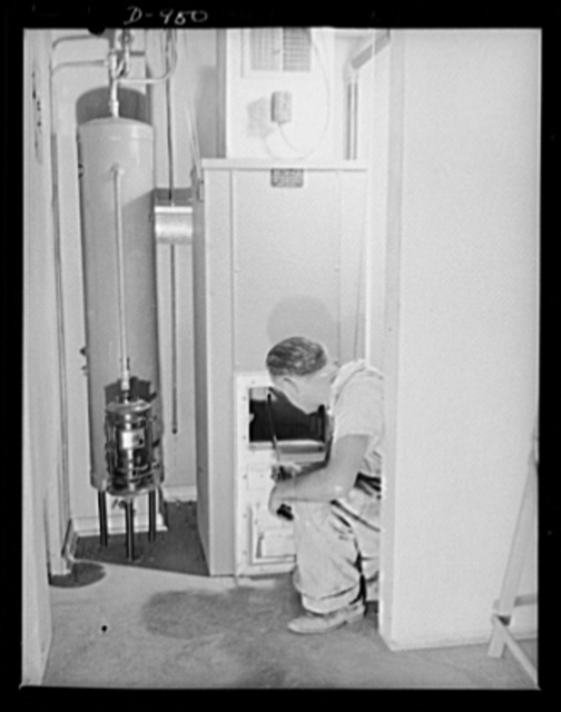 Defense housing, Erie, Pennsylvania. A workman installs a forced-air heating system in one of the 300 defense homes located at the Franklin Terrace housing project. This unit burns coal