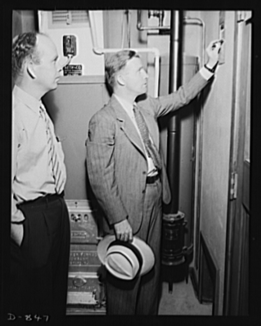 Defense housing, Erie, Pennsylvania. J.P. Kane, defense housing project manager at the Franklin Terrace project, explains the forced-air heating system of a defense home to B.J. Rogan, worker in the General Electric plant at Erie, Pennsylvania